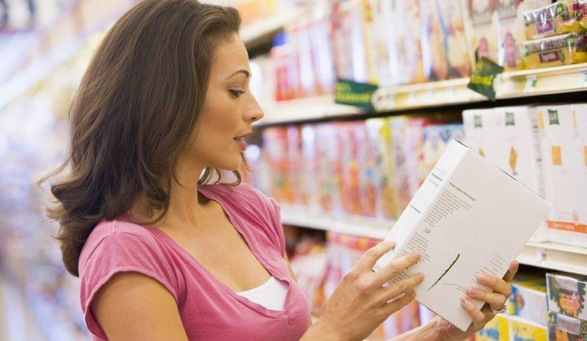 Woman in the grocery aisle looking at a box label